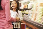 stock photo of trolley  - Close Up Of Mother Pushing Daughter In Supermarket Trolley - JPG