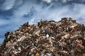 stock photo of scrap-iron  - Scrap metal ready for recycling over dark clouds - JPG