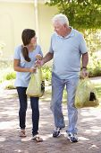 picture of grandfather  - Teenage Granddaughter Helping Grandfather With Shopping - JPG