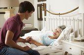 foto of visitation  - Teenage Grandson Visiting Grandmother In Bed At Home - JPG