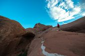 stock photo of cave woman  - Woman walking on a slickrock Cave Point Escalante Utah Horizontal - JPG