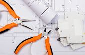 picture of electrical engineering  - Rolls of electrical diagrams electric fuse and work tools lying on construction drawing of house drawings for the projects engineer jobs - JPG