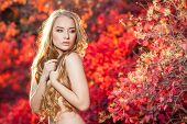 picture of chest hair  - young woman on a background of red and yellow autumn leaves with beautiful curly hair on his chest - JPG