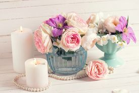 foto of violet flower  - Pink roses white jasmine and violet clematis flowers and candles on white wooden background - JPG