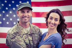 stock photo of reunited  - Handsome soldier reunited with partner against an american flag - JPG