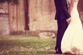 foto of hand kiss  - Close up of a bride and groom holding hands - JPG