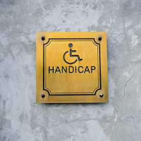 stock photo of handicapped  - Disabled Handicap Icon and wording Handicap Sign made from gold metal board - JPG