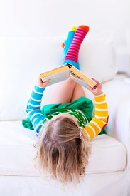 stock photo of couch  - Little girl reading a book relaxing on a white couch - JPG