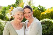 stock photo of mother daughter  - Mother with her daughter looking at the camera in the garden - JPG