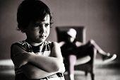 Fotografía antigua de estilo: niño enojado parado al frente de la chica relajada en la silla. Foto blanco y negro,