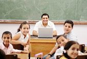 pic of tweeny  - Happy young teacher and children in classroom together - JPG