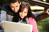 Young couple, male and female sitting in park and studying and workin together with notebook (laptop)