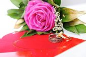 Love rose, for lover, on white with affiance (marriage) rings and red heart card