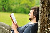 Young relaxed man reading book in nature, back on tree, meadow behind