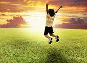 Gelukkige succesvolle winnaar kind springen op een mooie groene weide