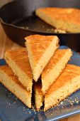 Stack Of Cornbread On Blue Plate With Black Skillet In Background