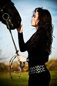 foto of black horse  - beautiful black hair woman and black horse outdoor day shot - JPG