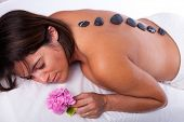 young beautiful woman in a spa enjoying a hot stone treatment
