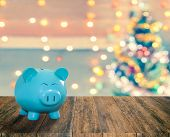 Blue Pig Bank On Wood Plank With Sparkle Blur Christmas Tree. You Can Apply For Blur Christmas Wallp poster