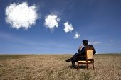businessman sitting in a chair thinking about the future the field