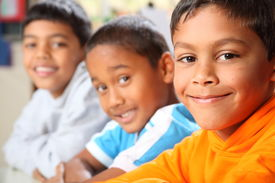 stock photo of school child  - Three happy smiling young school boys sitting in a row in classroom - JPG