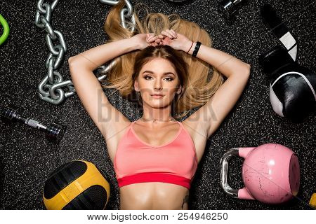 poster of Portrait Of Fit Brutal Athletic Young Cute Lady In Fashion Sportswear Laying Near Weights And Fitnes