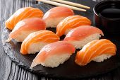 Постер, плакат: Freshly Cooked Sushi With Salmon And Tuna Soy Sauce Chopsticks Close up On A Black Slate Horizont
