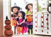 Happy Halloween! Three cute little laughing girls in witches costumes are coming to the house for sw poster