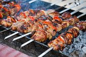 stock photo of flame-grilled  - Juicy slices of meat with sauce prepare on fire  - JPG