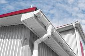 White Guttering On A Home With Red Roof Against Blue Sky. Plastic Guttering System. Guttering Draina poster