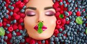 Beauty fashion model girl lying in fresh ripe fruits, berries and mint. Face in colorful berries clo poster