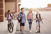 Diverse group of school kids talking and walking home from school together. Full length candid photo poster