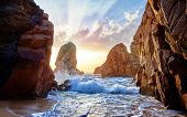 Sand beach among rocks on evening sunset. Ursa Beach near Cape Roca (Cabo da Roca) at Atlantic Ocean poster
