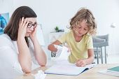 Stressed Psychotherapist Having A Headache During A Meeting With A Rebellious Child With Behavioral poster