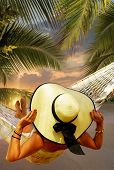 Woman in hat sitting in hammock on the beach. Travel and vacation concept. poster
