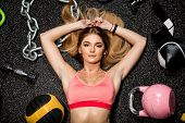 Portrait Of Fit Brutal Athletic Young Cute Lady In Fashion Sportswear Laying Near Weights And Fitnes poster