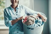 Young Smiling Woman Holds Basket Of Clean Clothes. Pretty Girl Caring Basket With Stack Of Fresh Clo poster
