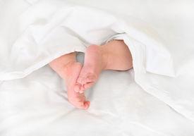 stock photo of sleeping baby  - Legs of sleeping baby on bed under blanket - JPG