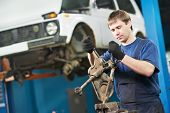 automotive mechanic worker tighten screw with spanner during automobile car maintenance at lever rep