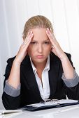 a young woman with migraine headaches and is sitting in an office.
