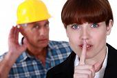 Female office worker making shush gesture