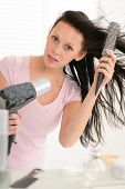 Brunette woman blow-drying long hair using round hairbrush