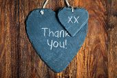 Thank you note written in chalk on a slate heart hanging on a wooden background