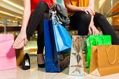 Two female friends with shopping bags having fun while shopping in a mall, the feet hurt already