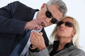 stock photo of swagger  - mature gentleman smoking cigar with blonde spouse showing off - JPG