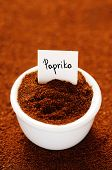 stock photo of pepper  - Ground paprika in a white ceramic bowl - JPG