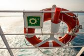 Lifebuoy With Sign On A Ferry Fence, With Sun And Sea In Backgro