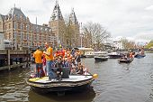 AMSTERDAM, NETHERLANDS - APRIL 30: People in orange celebrating in Amsterdam on the canals during the coronation of the new king Willem Alexander from the Netherlands on 30 april 2013