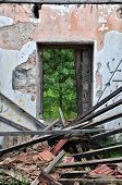 stock photo of collapse  - Collapsed roof chipped wall and open door with view to nature scene - JPG