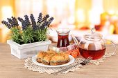 Sweet baklava on plate with tea on table in room